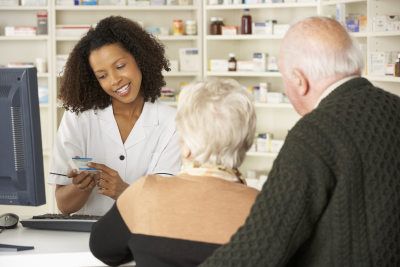 pharmacist giving a prescription to the old couple